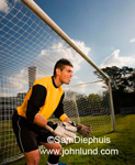 Sports photo of a goal keeper playing futbol or soccer in front of the goalie net.